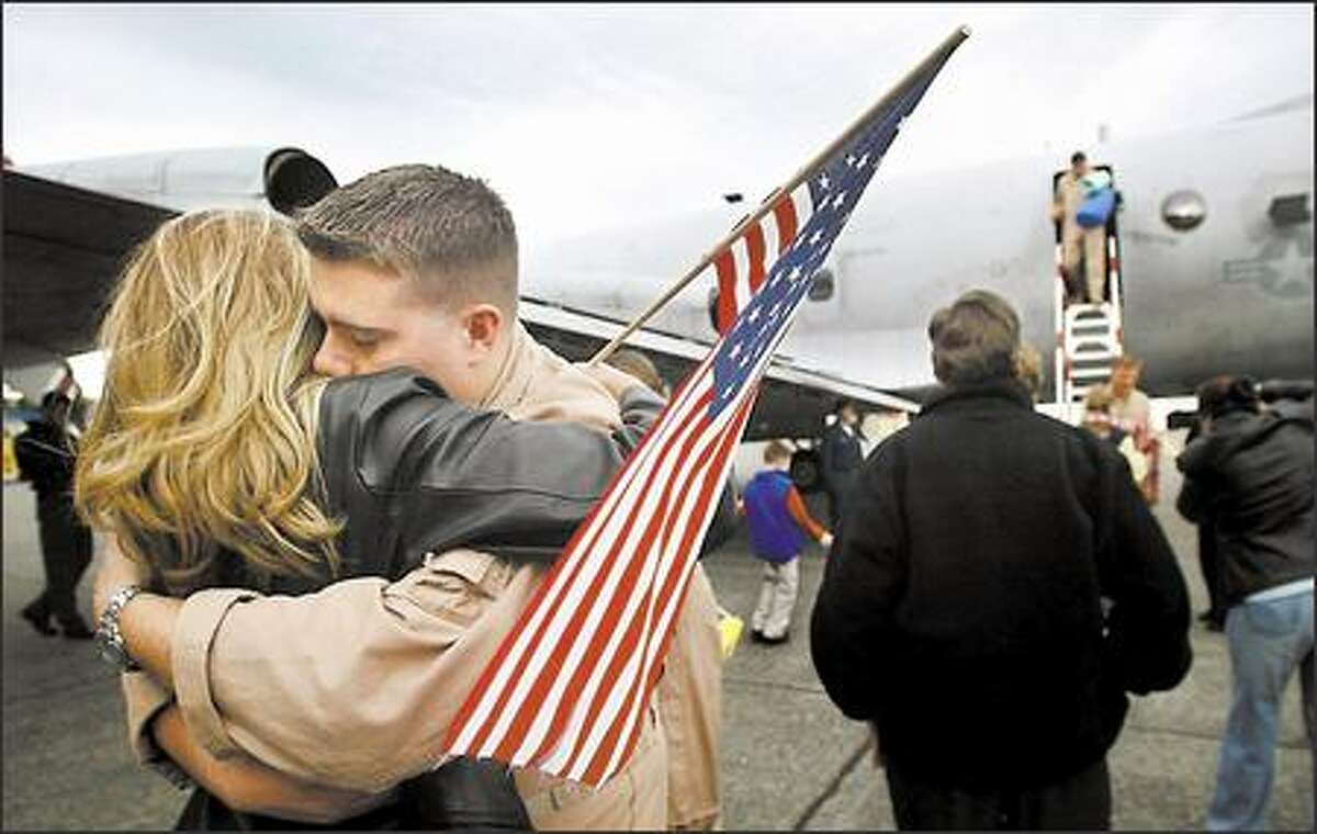 Phillip Hutchens hugs his wife, Casey, yesterday after landing at Naval Air Station Whidbey Island. The last of seven P-3C Orion aircraft from Patrol Squadron 40 returned from a six-month deployment to the Persian Gulf. The Fighting Marlins, as the squadron is known, provided surveillance and reconnaissance over Iraq and Afghanistan.