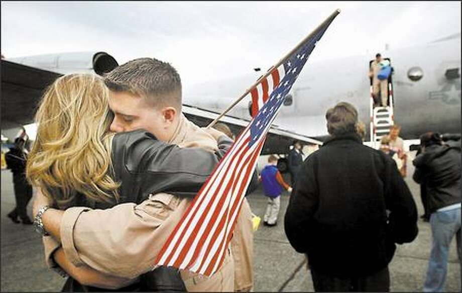 Phillip Hutchens hugs his wife, Casey, yesterday after landing at Naval Air Station Whidbey Island. The last of seven P-3C Orion aircraft from Patrol Squadron 40 returned from a six-month deployment to the Persian Gulf. The Fighting Marlins, as the squadron is known, provided surveillance and reconnaissance over Iraq and Afghanistan. Photo: Joshua Trujillo, Seattlepi.com / seattlepi.com
