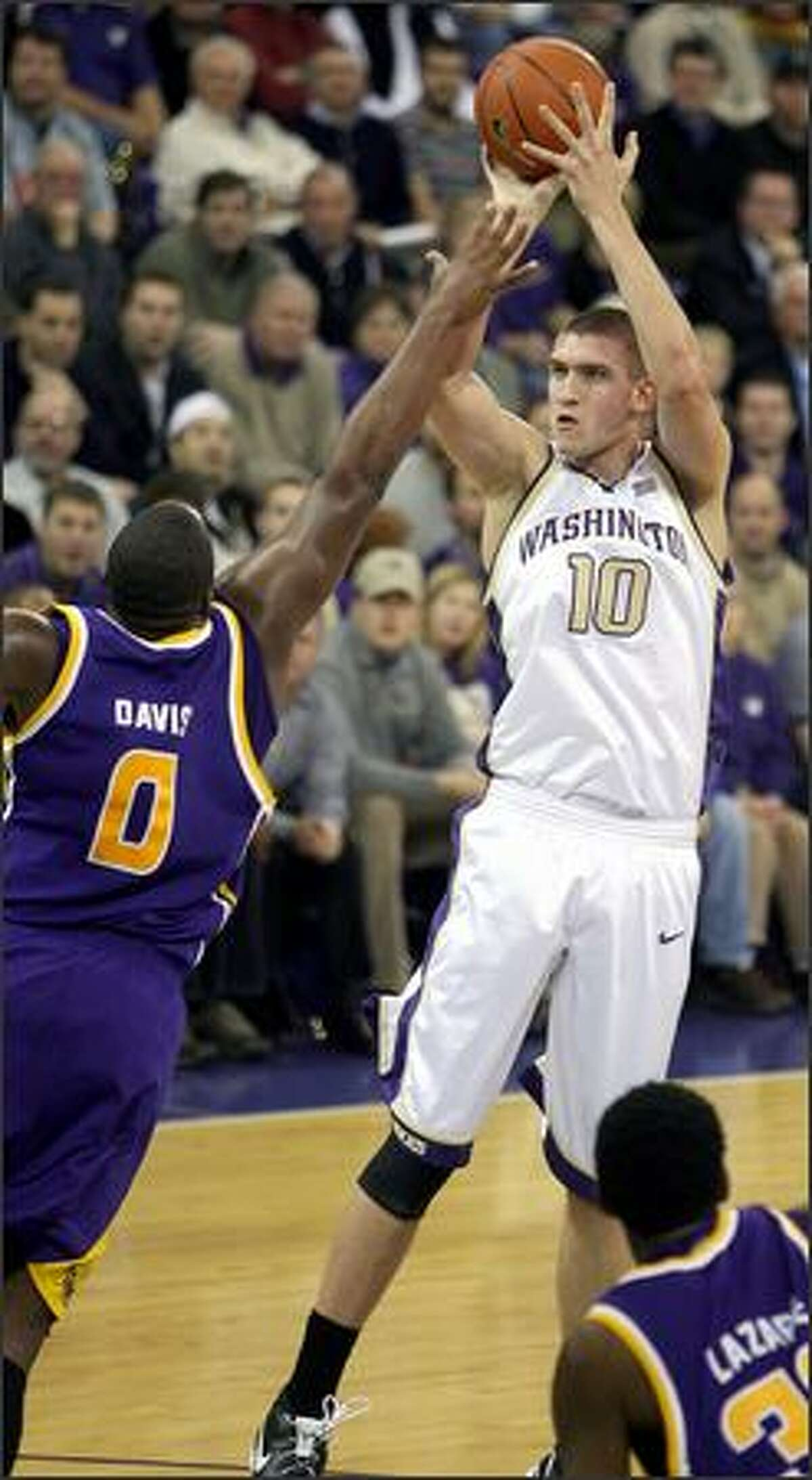 Washington's Spencer Hawes shoots and scores over LSU's Glen Davis during the first half of Wednesday's game. Hawes scored 23 points as the Huskies pulled a 88-72 upset.