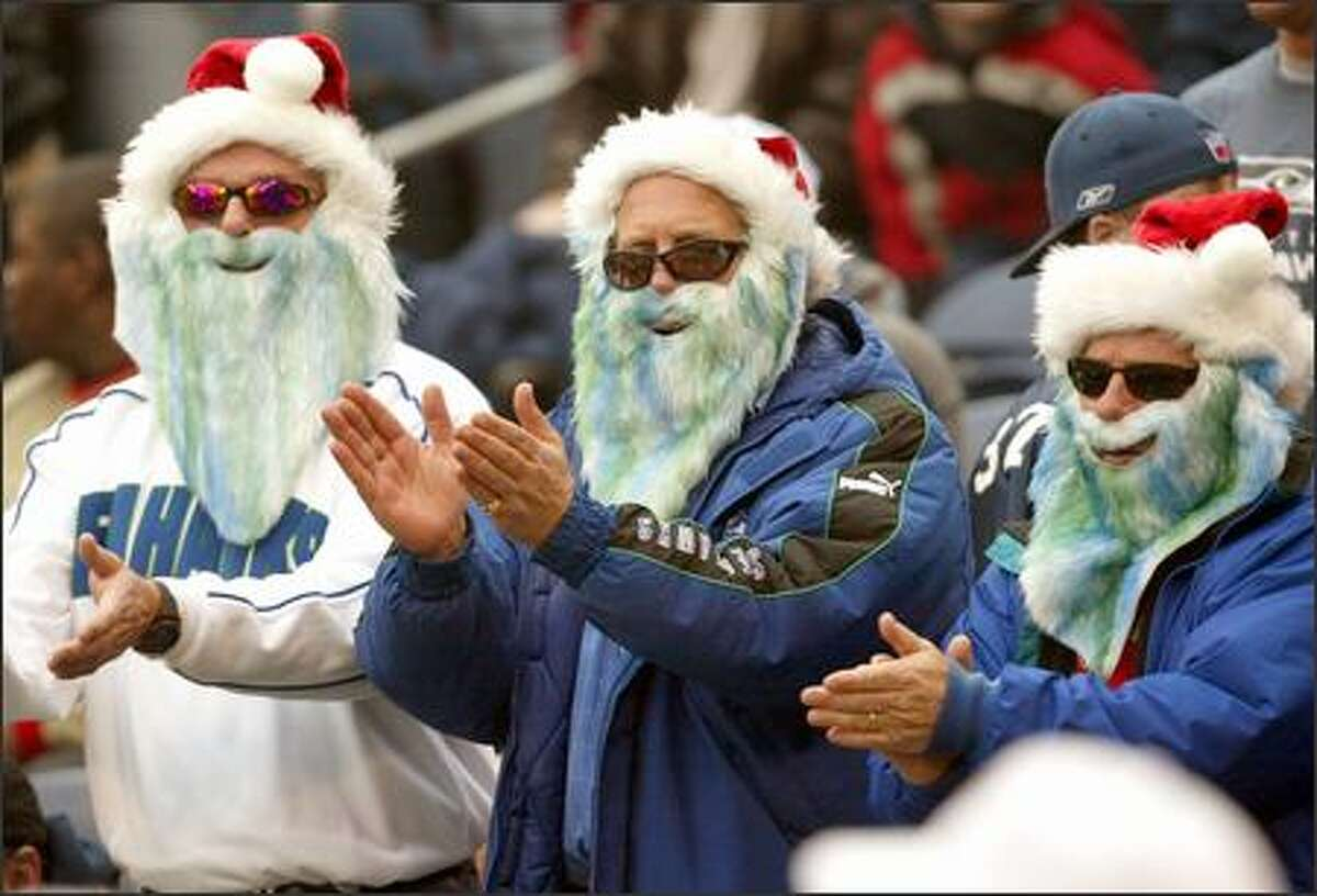 Seattle fans (left to right) Larry Beck, of Lynnwood, Dave Nelson, of Monroe, and Duane Parrish, of Mukilteo, sport Seahawks-hued Santa Claus beards for the game.