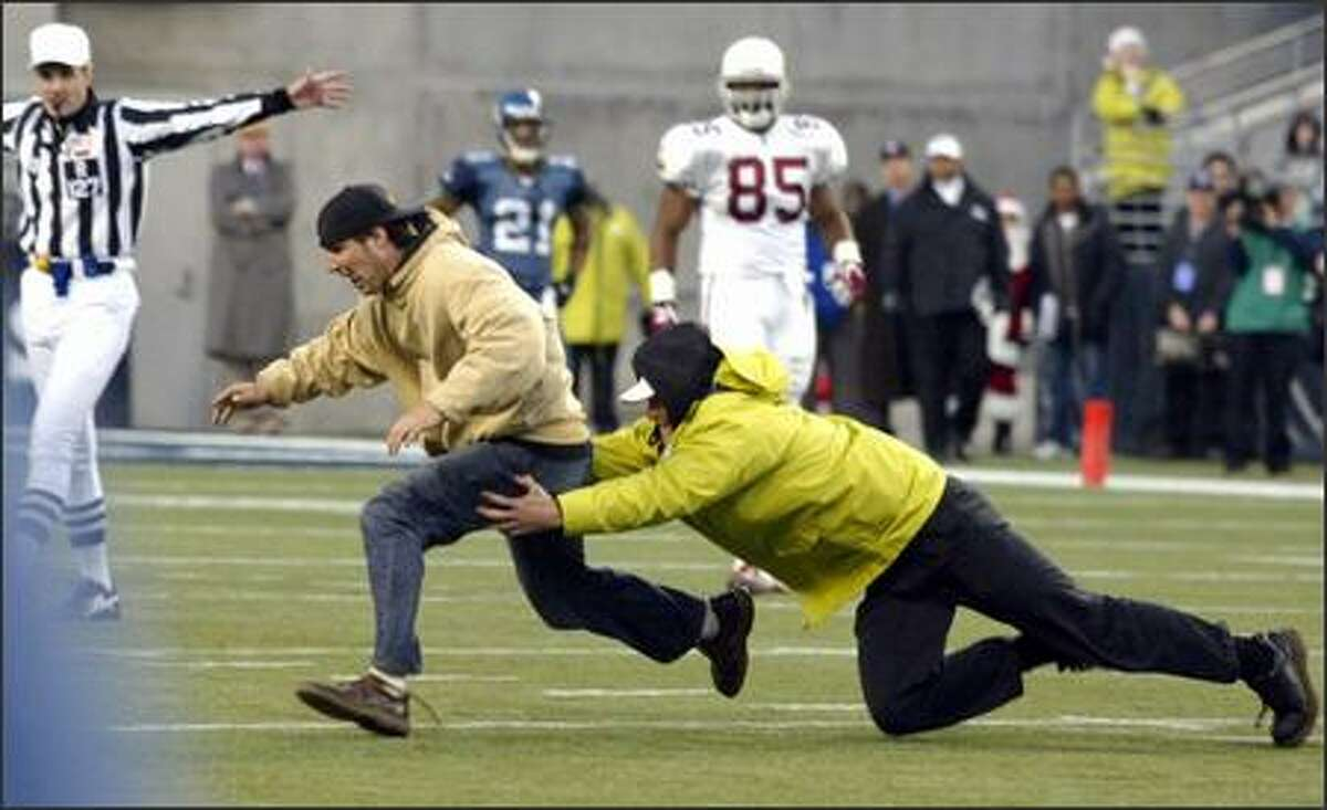 A fan who ran onto the field during the final seconds of the game is tackled by security guards at the 30-yard line.