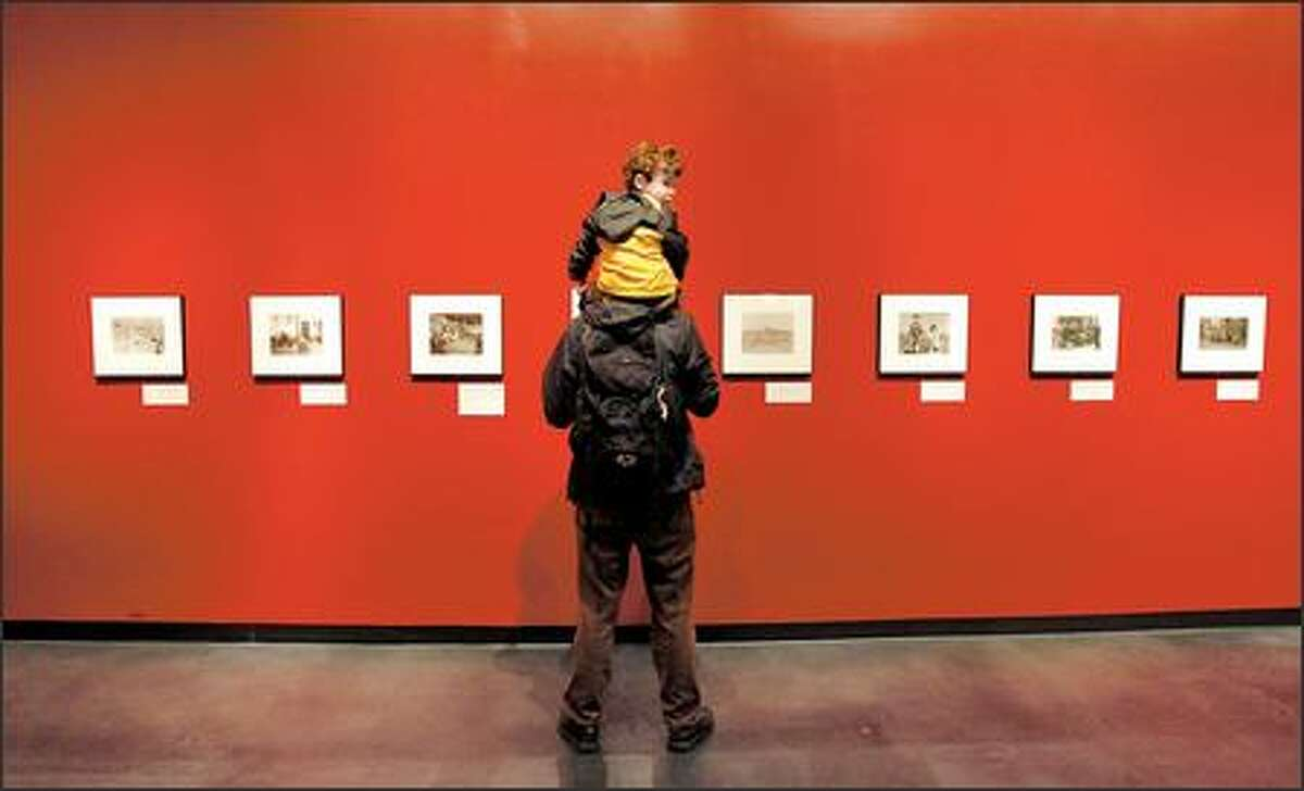 Patrick Collins and his son, Felix Malot-Collins, checks out a photo show called