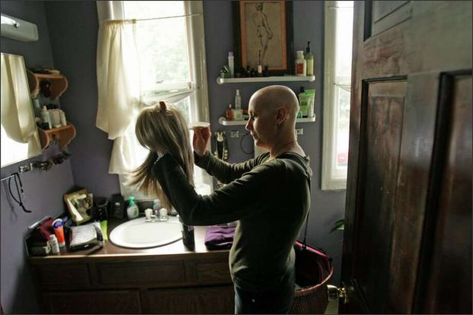 Kristina Southard, a leukemia patient and recent recipient of a bone marrow transfer, combs out her synthetic hair wig at her Fremont home. Before starting chemo-therapy Southard had blonde, shoulder length hair. Photo: Mike Kane, Seattle Post-Intelligencer / Seattle Post-Intelligencer