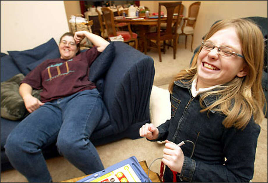 Samantha McAfee, 9, and mom Michele McAfee share a mirthful moment at home. Samantha's grandma has AIDS, and that has taken a toll on the family. Photo: Meryl Schenker, Seattle Post-Intelligencer / Seattle Post-Intelligencer