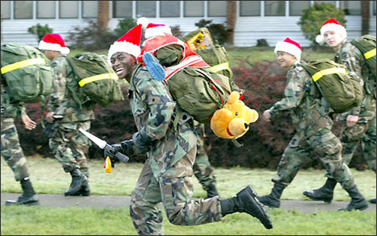 Army Spc. Michael Awoyomi and other soldiers from the 555th Engineer group at Fort Lewis trot along South Tacoma Way during their 12th Annual Christmas Road March to the Eugene P. Tone School in South Tacoma. About 100 soldiers took part Monday in the 13-mile march from their base through the streets of Lakewood and Tacoma to deliver clothes and toys to the 40-45 students at the alternative school designed to accommodate homeless children.