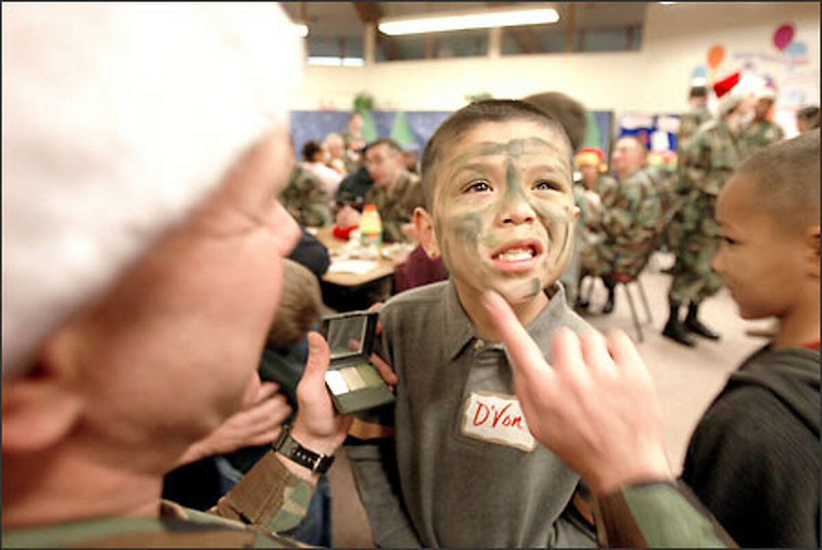 D'Von Harrison, 6, although not a student at Eugene P. Tone School, is on hand to get a camouflage look courtesy of Sgt. Maj. Tony Cady. D'Von is a student at McCarver Elementary and lives in shared housing with his mother.