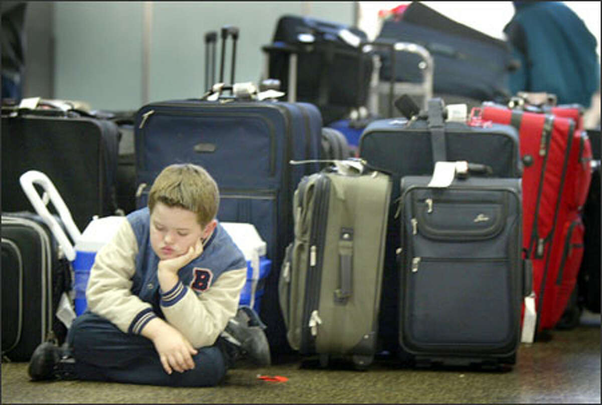 Alex Ryan, 8, of San Diego appears bored as he waits during a baggage backup at Sea-Tac International Airport. Ryan was traveling to visit family in Sequim.