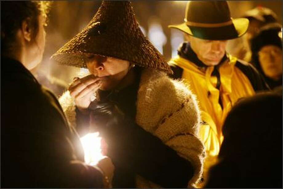 Mary Lou Salter lights sage during a vigil Wednesday near where Davina Garrison, who was homeless, was killed on Thanksgiving Day under the Alaskan Way Viaduct. Photo: Dan DeLong, Seattle Post-Intelligencer / Seattle Post-Intelligencer