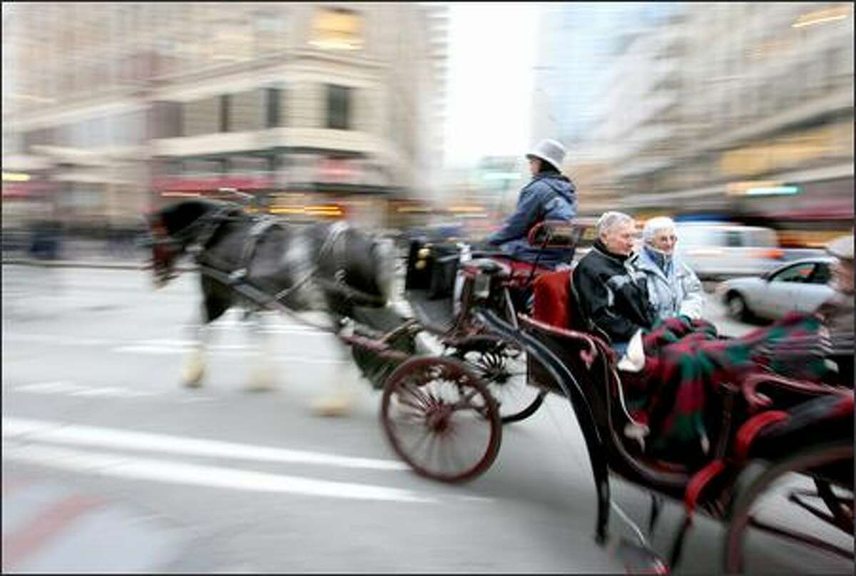 Ray and Dixie Christoffersen of Edmonds ride on a horse-drawn carriage driven by Millie Haggin along with friends Jack and Mary Neilsen (not shown) through downtown Seattle on Friday, Dec. 22. Both couples said the ride was one of their reasons for venturing into the Emerald City to shop before Christmas.