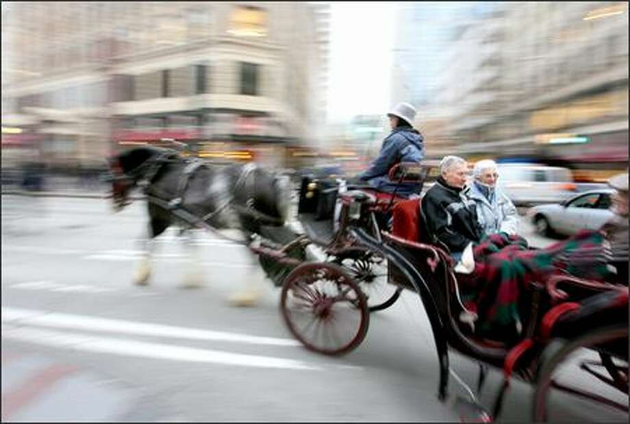 Ray and Dixie Christoffersen of Edmonds ride on a horse-drawn carriage driven by Millie Haggin along with friends Jack and Mary Neilsen (not shown) through downtown Seattle on  Friday, Dec. 22.  Both couples said the ride was one of their reasons for venturing into the Emerald City to shop before Christmas. Photo: Scott Eklund, Seattle Post-Intelligencer / Seattle Post-Intelligencer