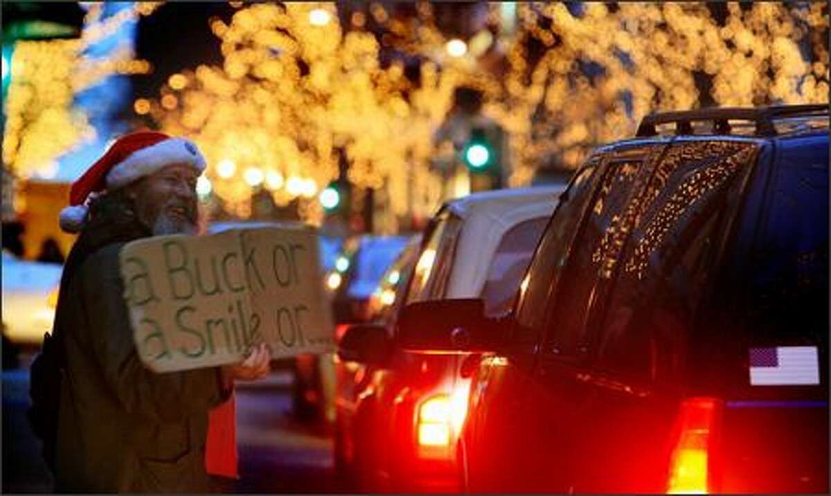 Sporting a Santa hat for the season, Scott Wilson of Seattle vies for the attention of motorists stuck in rush-hour traffic along Fifth Avenue in downtown Seattle three days before Christmas. He said he was collecting money so he could buy a dinner of Chinese food for his mother.