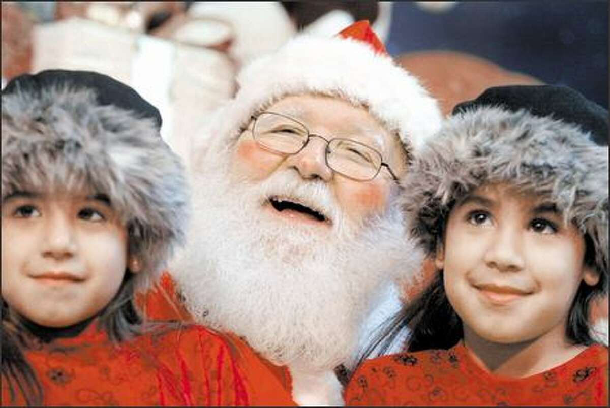 On Myron Colson's first day on the job as Santa Claus, he poses at Bellevue Square mall with sisters Erin Jones, 5, and Jennifer, 7, of Fall City.