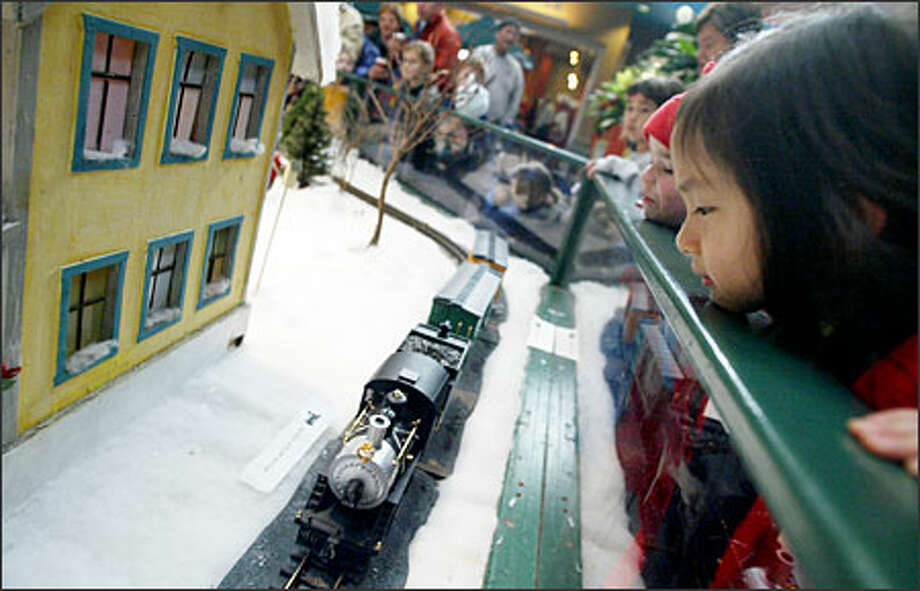 Liz Han, 4, watches the Seattle Center's model train cruise around a miniature 19th-century village set up in the Center House yesterday. The display has been a part of the holidays at the Seattle Center since 1974, according to the Center's Web site. This year, the display will be up until Jan. 2 Photo: Joshua Trujillo, Seattlepi.com / seattlepi.com