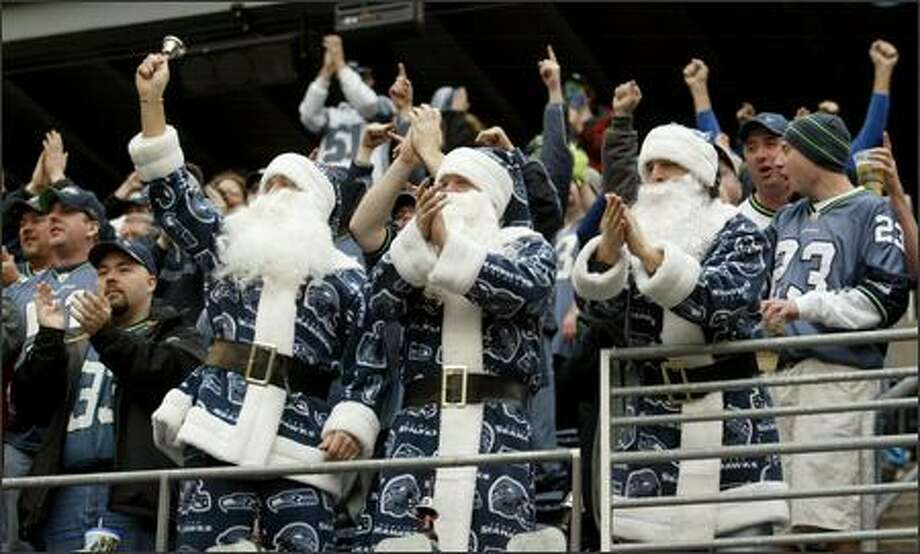 The Seahawk Santas enjoy the action during the Christmas Eve game against the Colts. The Seahawks won 28-13. Photo: Scott Eklund, Seattle Post-Intelligencer / Seattle Post-Intelligencer