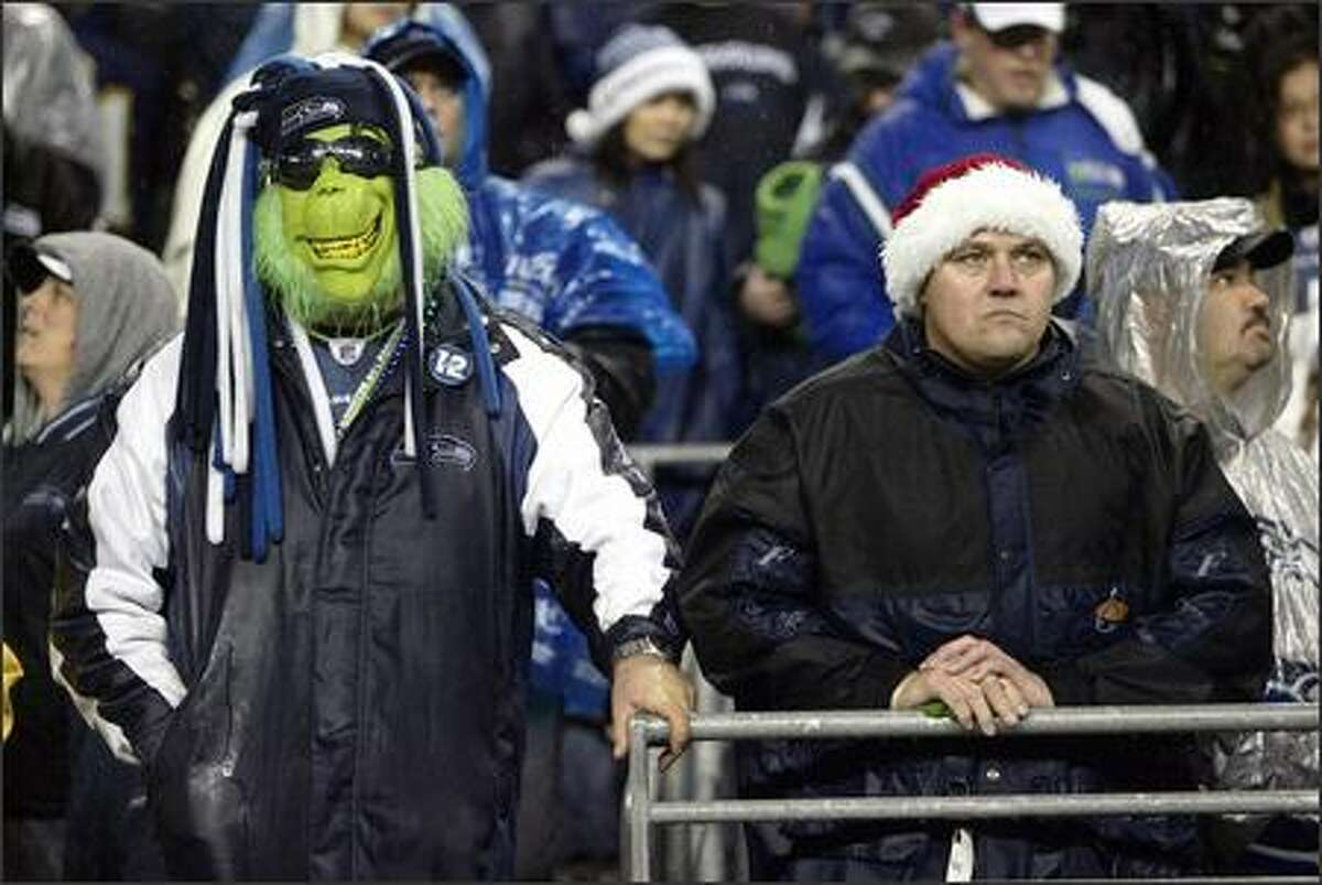 Mark Bowman, left, of Browns Point looks gleeful in his Grinch mask but the man beside him looks decidedly less happy as they watch the final seconds tick off during the Seahawks' 20-17 loss to the San Diego Chargers at Qwest Field on Christmas Eve 2006.