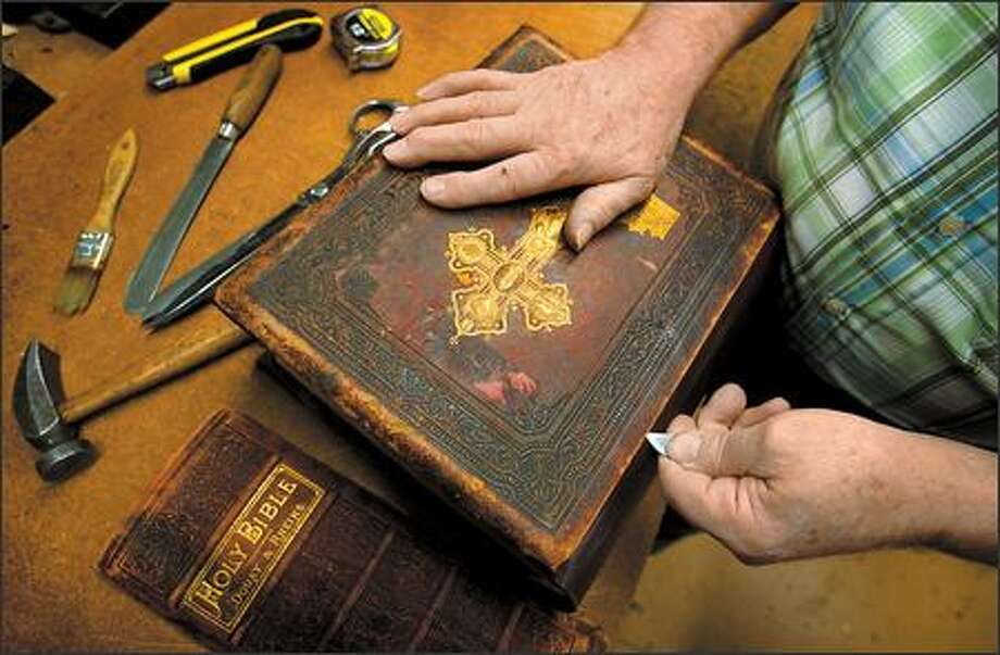 "Phil Goldader of Phil's Custom Binding in Seattle repairs an old Bible. The restoration takes about two weeks. ""You get them in here, they are such a mess,"" Phil said. Photo: Scott Eklund, Seattle Post-Intelligencer / Seattle Post-Intelligencer"