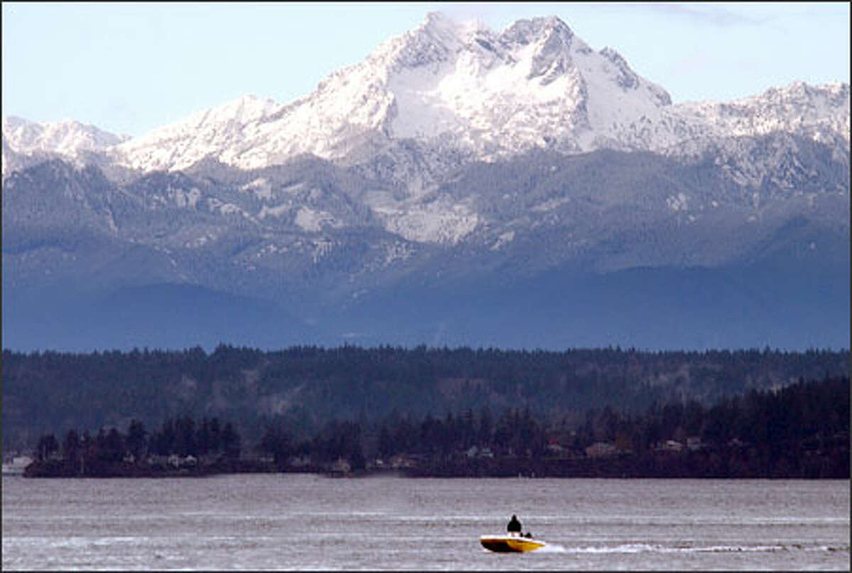 A dusting of fresh snow lends a fairy-tale quality to the Olympic Mountains, rising above a boater on Elliott Bay.