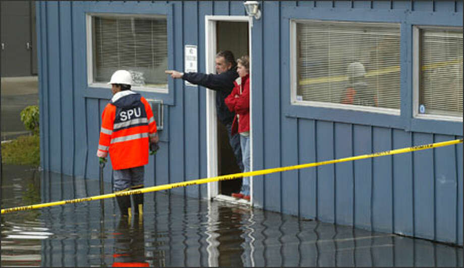 Bill and Nancy Neisinger, owners of Associated Roofing Inc. in Lake City, describe to a city worker where water from Thornton Creek bubbled up and flooded their building. Photo: Phil H. Webber, Seattle Post-Intelligencer / Seattle Post Intelligencer