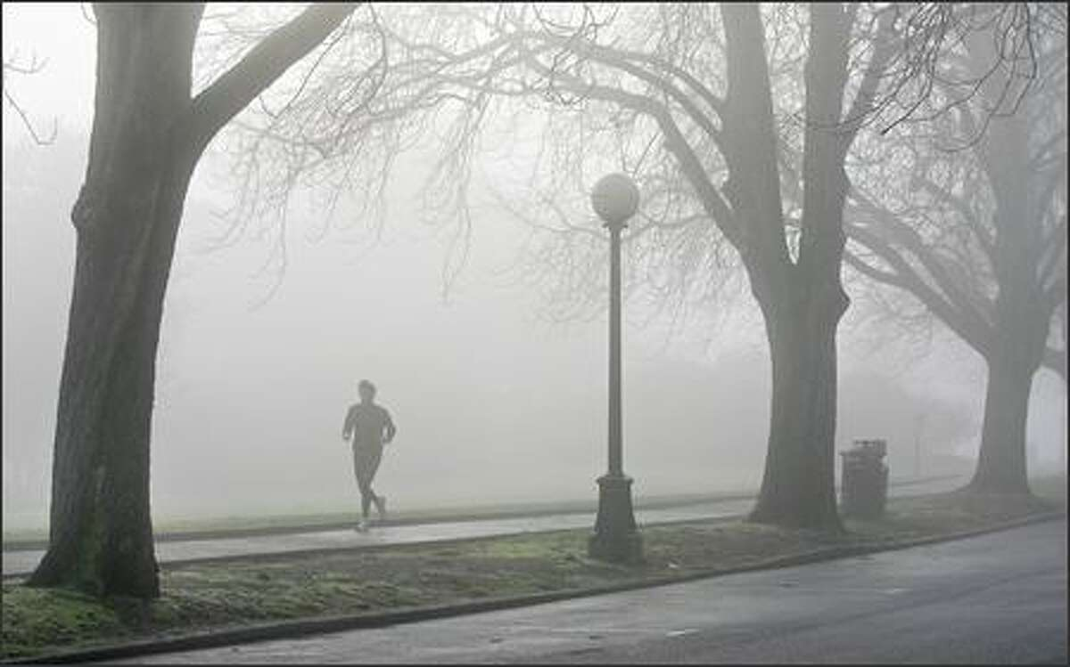 A man jogs in a foggy Volunteer Park in Seattle's Capitol Hill neighborhood.
