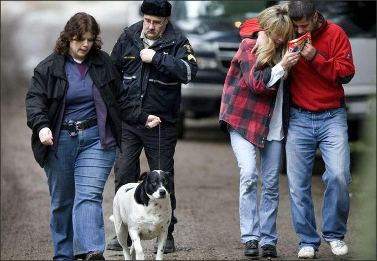King County Sheriff's Detective Robin Cleary leads a dog, followed by King County Animal Control Sgt. Steve Couvion, near the house on the outskirts of Carnation where six people were shot to death on Christmas Eve. At right are Mary and Ben Anderson, relatives of those killed.