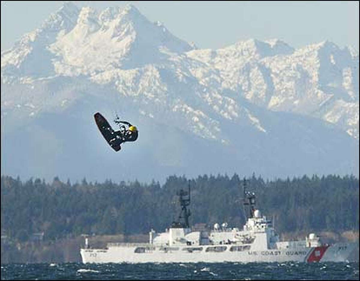 With the Olympic Mountains and a Coast Guard ship providing the dramatic backdrop, Adam Vance of Seattle flies high above Puget Sound while kite surfing near Meadow Point.