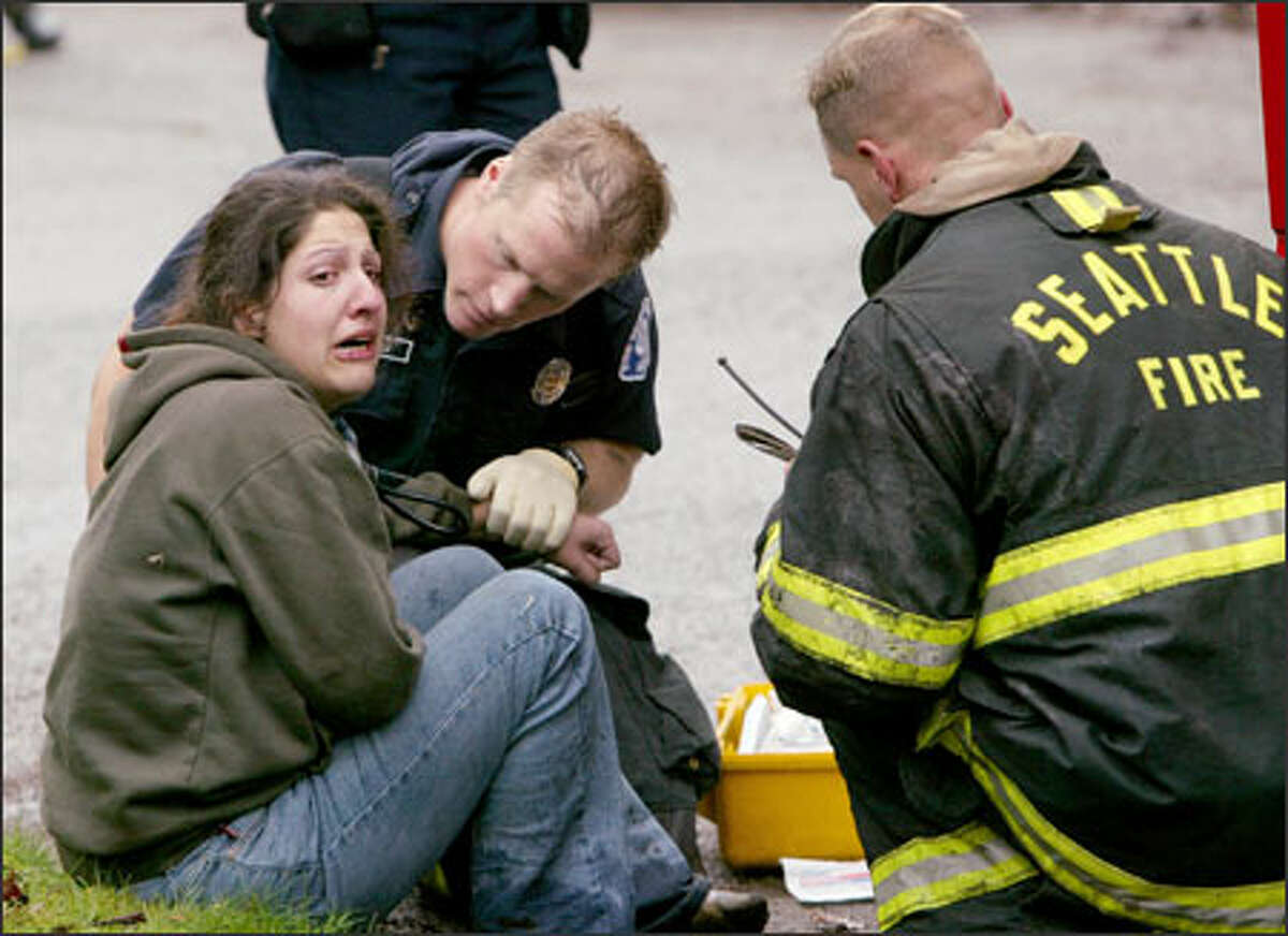 Firefighters tend to one of the victims of a fire that tore through a rooming house in Seattle's University District on Thursday. She suffered an injured foot.