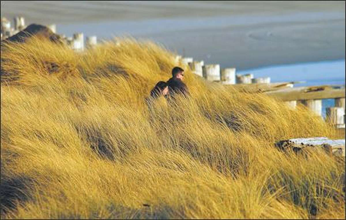 Tall sea grass surrounds a couple near the south jetty at Fort Stevens State Park west of Astoria.