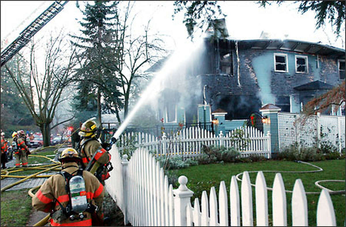Seattle firefighters battle an early-morning fire on 13th Avenue East on Capitol Hill yesterday. The blaze destroyed the two-story rental house. Investigators say an overheated extension cord in the living room sparked the fire at 6:50 a.m. Several items were plugged into the cord, including lights for a Christmas tree, a Fire Department spokeswoman said.