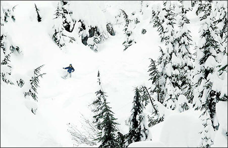 A snowboarder makes his own route in the backcountry near Alpental ski resort in Snoqualmie Pass yesterday. More snow is expected from the storm that's moving through the region. Photo: Dan DeLong, Seattle Post-Intelligencer / Seattle Post-Intelligencer