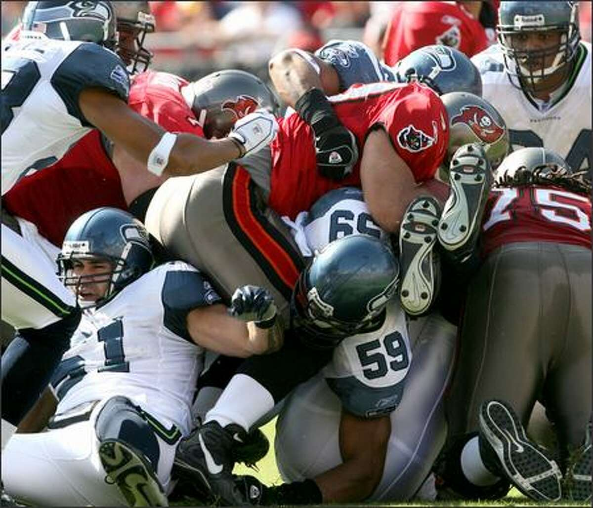 The Seahawks defense gang-tackles Mike Alstott for no gain in the first quarter of Sunday's game against the Tampa Bay Buccaneers. Seattle won 23-7.