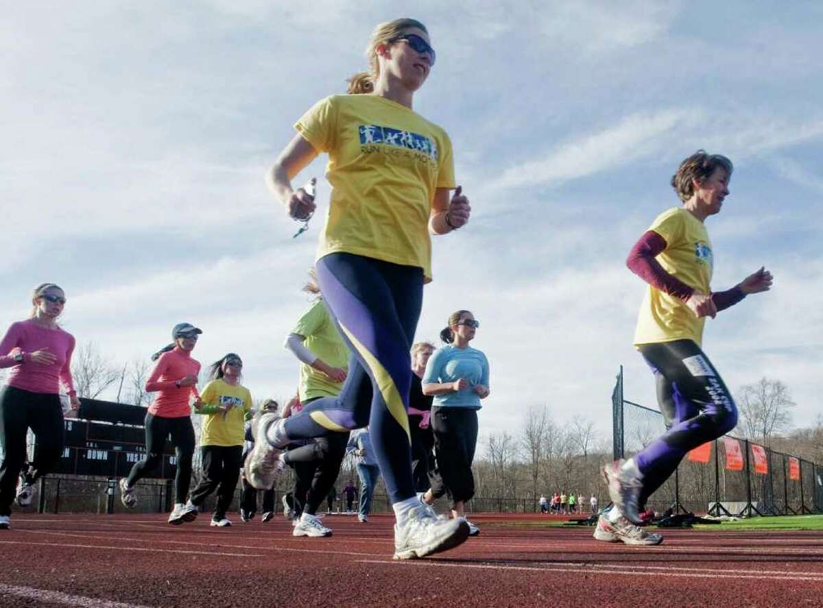 Ridgefield trainers Morgan Cotter, left, and Leslie Krichko-Townsend lead an advanced group of women runners on the Ridgefield High School track practicing for the upcoming Run Like A Mother 5K race. Photo taken Sunday, April 3, 2011