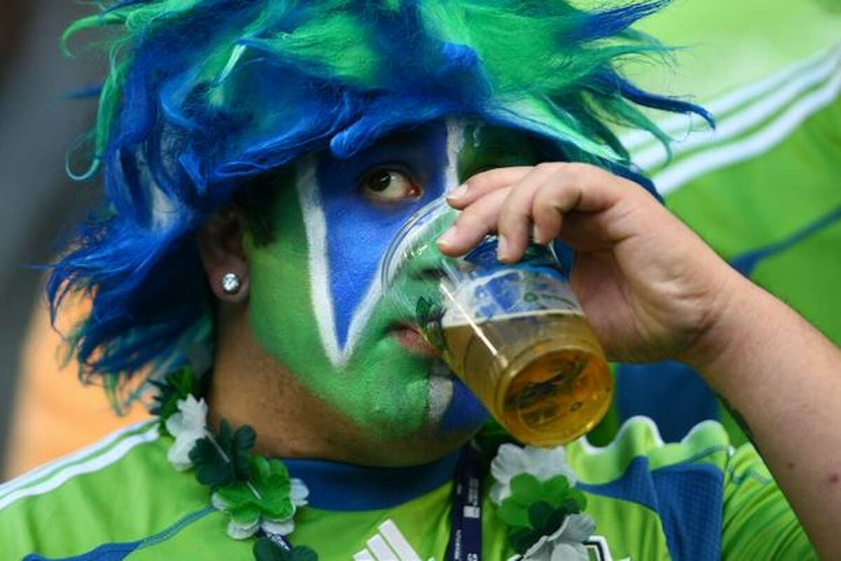 A Sounders fan imbibes before the start of the first half of their match against the New England Revolution on Thursday at Qwest Field in Seattle.