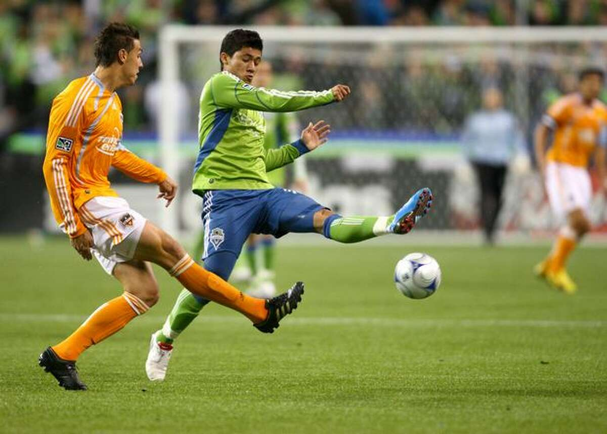 Fredy Montero, right, tries to get control of the ball from Houston's Geoff Cameron (20) in the first half during the first round of the MLS playoffs at Qwest Field in Seattle on Thursday.
