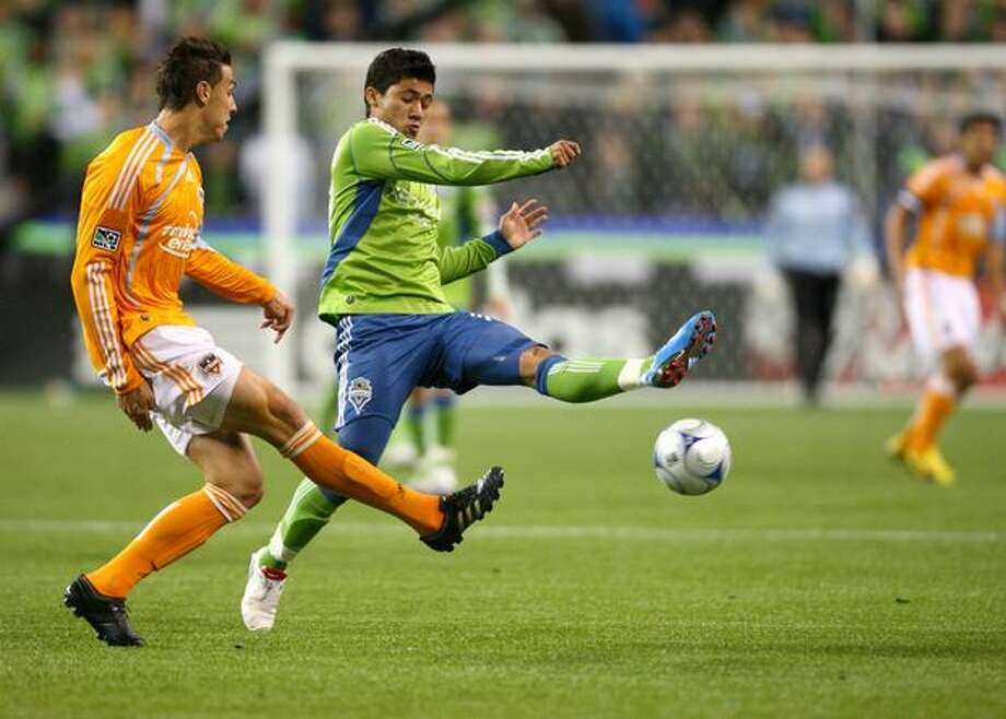 Fredy Montero, right, tries to get control of the ball from Houston's Geoff Cameron (20) in the first half during the first round of the MLS playoffs at Qwest Field in Seattle on Thursday. Photo: Joshua Trujillo, Seattlepi.com / seattlepi.com