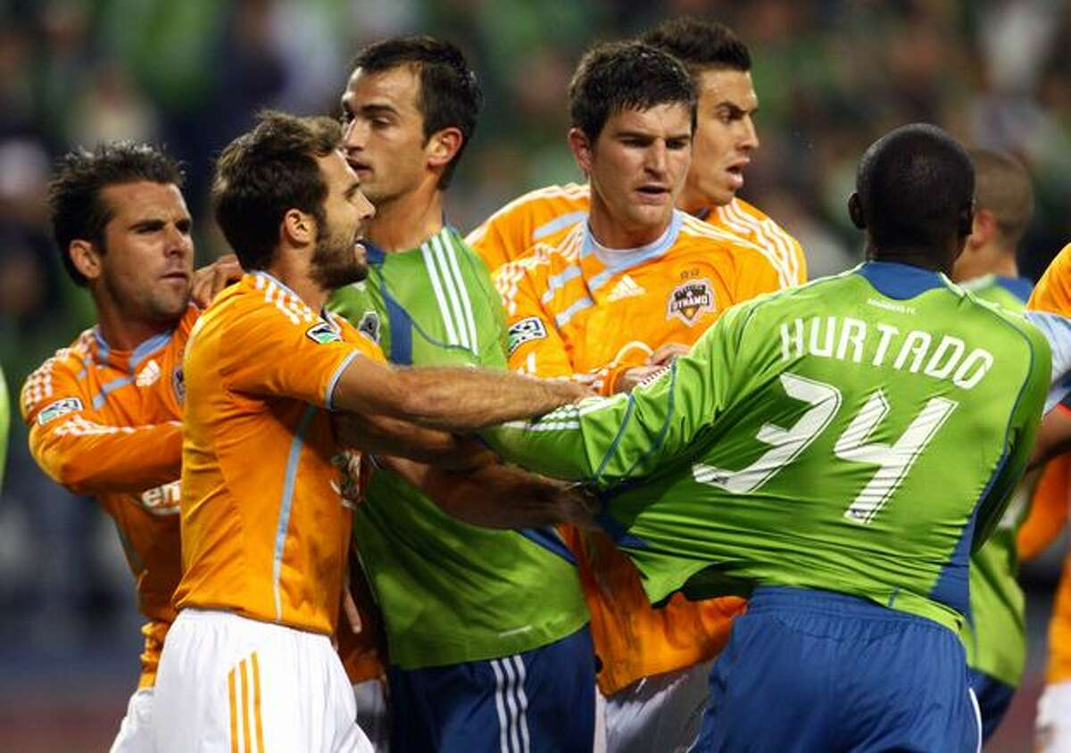 From left, Houston's Mike Chabala and Brian Mullan, Seattle's Patrick Ianni, Houston's Bobby Boswell and Geoff Cameron and Sounders player Jhon Kennedy Hurtado are involved in a shoving match that resulted in two yellow cards in the first half.