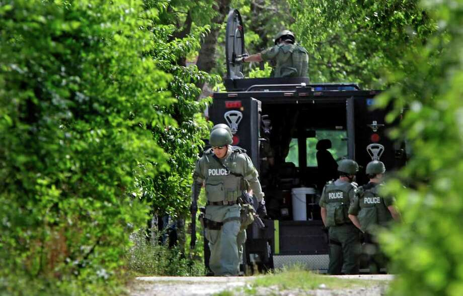 Metro daily  - SWAT team members position themselves near a house at 214 N. Pinto where a man is held up after shooting at police officers.  Monday, April 4, 2011. Photo Bob Owen/rowen@express-news.net Photo: Bob Owen, San Antonio Express-News / rowen@express-news.net
