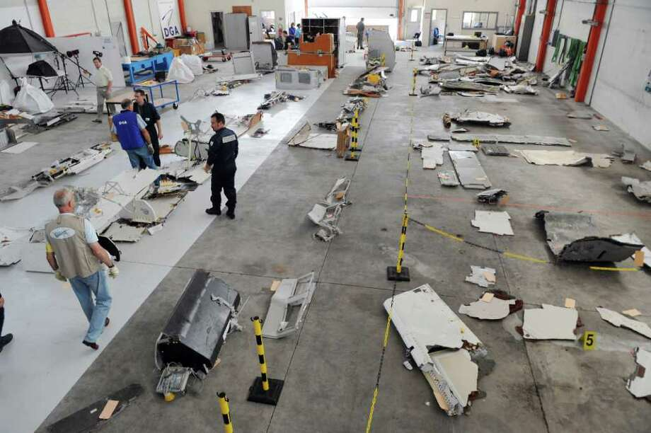 Investigators of the BEA (the French bureau leading the crash investigation) inspect debris from the mid-Atlantic crash of Air France flight 447 on July 24, 2009 at the CEAT aeronautical laboratory in Toulouse, southern France. The Air France flight from Rio to Paris came down during the night of May 31 to June 1, 2009 during a storm, with the loss of all 228 people on board. The BEA said in a report, based on an initial study of the fragments, that the Airbus A330 was intact when it hit the ocean, but that the cause of the crash was still unknown. Photo: ERIC CABANIS, AFP/Getty Images / 2010 AFP