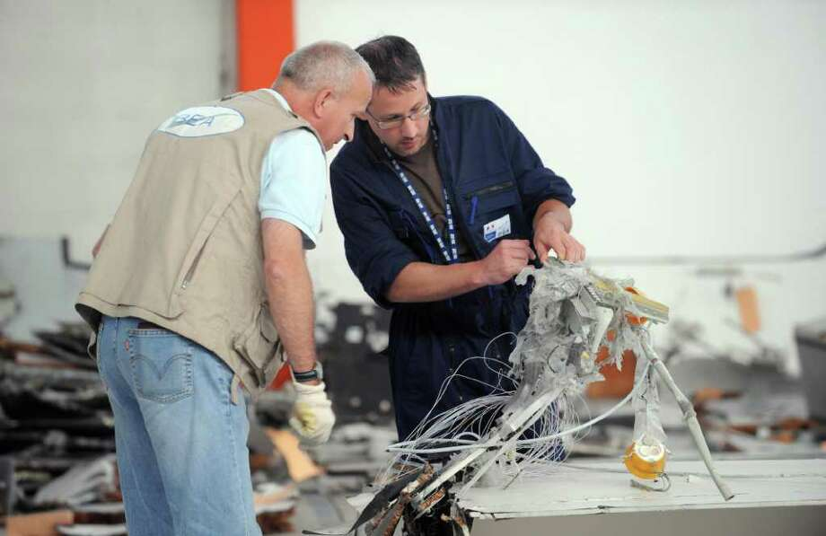 An investigator (left) of the BEA (the French bureau leading the crash investigation) and a member of the CEAT aeronautical laboratory inspect debris from the mid-Atlantic crash of Air France flight 447 on July 24, 2009 at the CEAT headquarters in Toulouse, southern France. The Air France flight from Rio to Paris came down during the night of May 31 to June 1, 2009 during a storm, with the loss of all 228 people on board. The BEA said in a report, based on an initial study of the fragments, that the plane was intact when it hit the ocean, but that the cause of the crash was still unknown. Photo: ERIC CABANIS, AFP/Getty Images / 2009 AFP