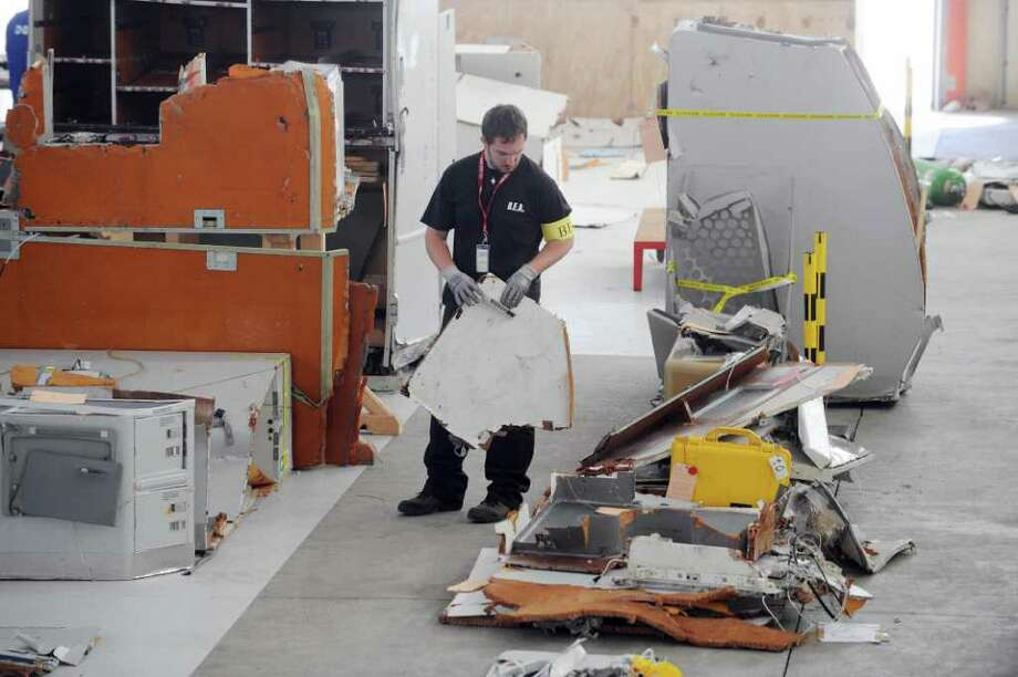 An investigator of the BEA (the French bureau leading the crash investigation) inspects debris from the mid-Atlantic crash of Air France flight 447 on July 24, 2009 at the CEAT aeronautical laboratory in Toulouse, southern France. The Air France flight from Rio to Paris came down during the night of May 31 to June 1, 2009 during a storm, with the loss of all 228 people on board. The BEA said in a report, based on an initial study of the fragments, that the Airbus A330, was intact when it hit the ocean, but that the cause of the crash was still unknown. Photo: ERIC CABANIS, AFP/Getty Images / 2009 AFP