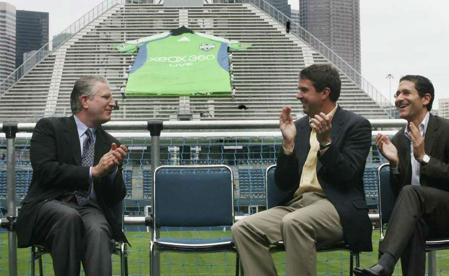 From left: Tod Leiweke, CEO of Vulcan Sports and Entertainment; Robbie Bach, president of the Microsoft's Entertainment and Devices Division; and Adrian Hanauer, Seattle Sounders minority owner and general manager, are shown after the unveiling of a giant Sounders FC jersey at Qwest Field in Seattle on May 28, 2008. The Seattle Sounders FC announced a multi-year sponsorship with Microsoft and Xbox 360. (seattlepi.com file) Photo: Dan DeLong, Seattle Post-Intelligencer / Seattle Post-Intelligencer