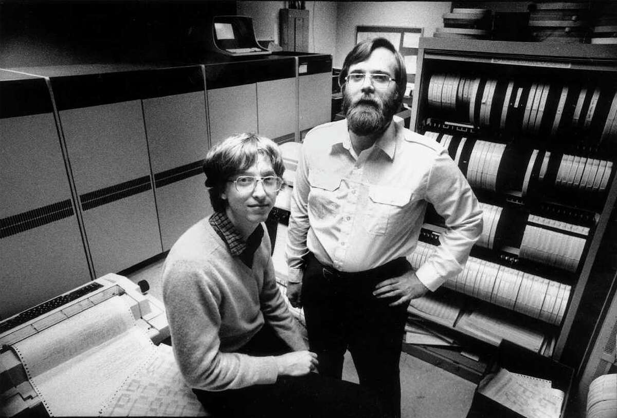 In 1981, computers the size of refrigerators and cabinets of tapes for reel-to-reel computer tape drives lined the walls in the small offices of Microsoft founders Bill Gates, left, and Paul Allen in Bellevue. In 1981 Microsoft employed 85 people. (AP Photo/Eastside Journal, Jim Hallas)