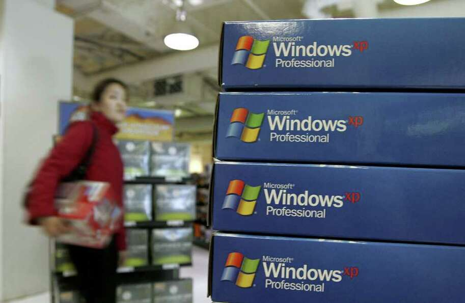 A customer walks near a display of Microsoft Windows XP software at a CompUSA store March 22, 2006,