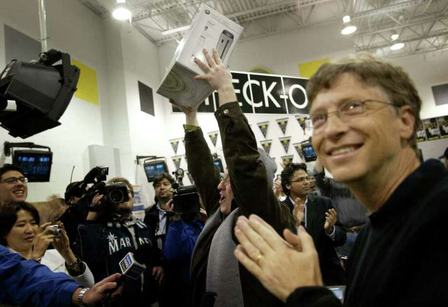 Bill Gates is all smiles as Dan Friedman, 26, holds up the first Xbox 360 sold at Best Buy in Bellevue during the Xbox 360 launch party on Nov. 21, 2005. (Joshua Trujillo/seattlepi.com file) Photo: JOSHUA TRUJILLO, SEATTLE POST-INTELLIGENCER  / SEATTLE POST-INTELLIGENCER