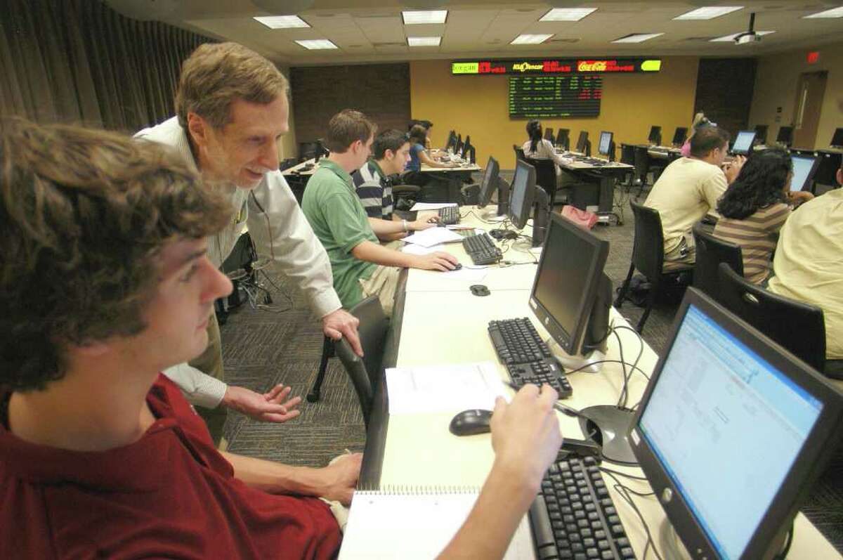 Fairfield University professor Dr. Michael Tucker answers student Keith Lennon's question in a classroom for Business Education Simulation and Trading, known as a BEST classroom. College-bound students, credit card users and employers looking to hire professionals are among the Connecticut residents whose email addresses may have been accessed by hackers who broke through the firewall of Dallas-based advertising firm Epsilon.