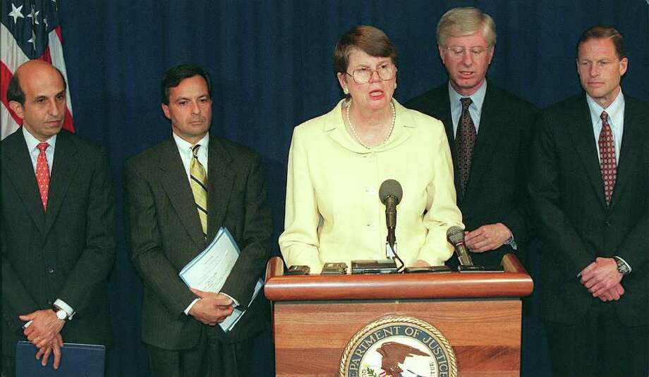 U.S. Attorney General Janet Reno, center, speaks to reporters during a press conference May 18, 1998, in Washington, D.C., concerning the filing of an antitrust suit by the U.S. government -- and attorneys general from 20 US states and the District of Columbia -- against computer software giant Microsoft. The suit charged Microsoft with abusing its corporate power and squashing competition in the software market. (TIM SLOAN/AFP/Getty Images) Photo: TIM SLOAN, Seattlepi.com / AFP