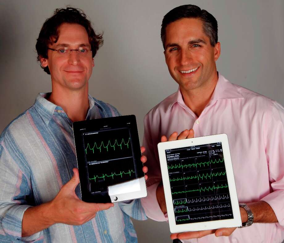 Dr. Cameron Powell, AirStrip Technologies' president and chief medical officer (right) and Trey Moore, chief technology officer, hold iPads displaying their latest app called AirStrip Cardiology. Photo: Kin Man Hui/kmhui@express-news.net