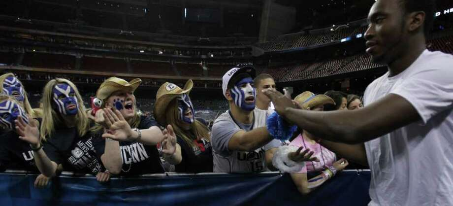 Connecticut fans cheer as Connecticut center Alex Oriakhi (34) comes into the stadium to warm up before the NCAA National Championship at Reliant Stadium on Monday, April 4, 2011, in Houston.  ( Karen Warren / Houston Chronicle ) Photo: Karen Warren, Houston Chronicle For The Connecticut Post / Houston Chronicle for the Connecticut Post