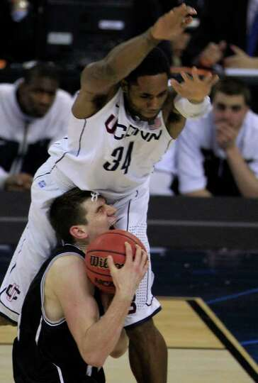 Butler center Andrew Smith (44) is run over by Connecticut center Alex Oriakhi (34) while driving to