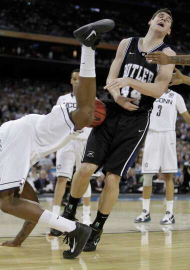 Connecticut center Alex Oriakhi (34) tumbles over Butler center Andrew Smith (44) during the first h