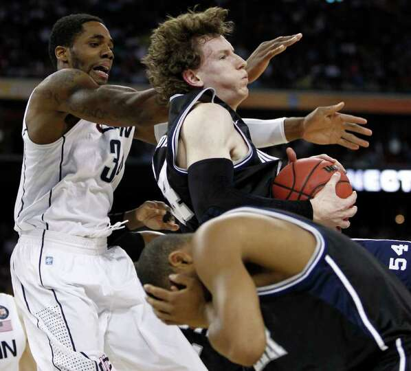 Butler forward Matt Howard (54) pulls down a rebound against Connecticut center Alex Oriakhi (34) du